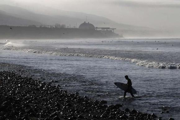 The darkened San Onofre nuclear power plants stands in the distance as a surfer walks from the water.