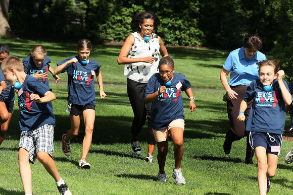 First lady Michelle Obama runs with a rubber ball under her chin while working out with local students on the South Lawn of the White House.
