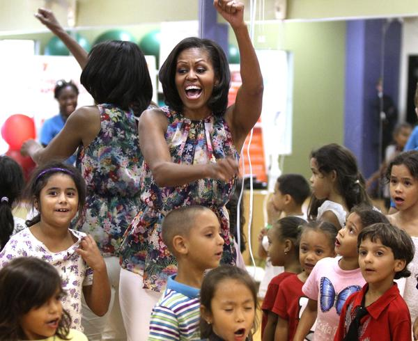 First Lady Michelle Obama dances with kids during an unannounced visit to the Blanchard Park YMCA in east Orlando, Tuesday July 10, 2012. Obama later rallied students at the University of Central Florida.