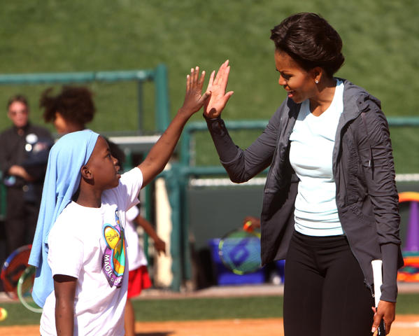 First Lady Michelle Obama high fives a student after playing tennis   during her visit to the ESPN Wide World of Sports Complex at Walt Disney World, in Lake Buena Vista, Fla., Saturday, February 11, 2012.