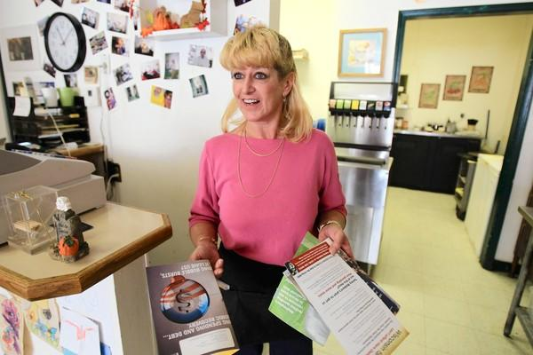 Sunrise Cafe owner Kathy Miller shows how many political mailings she receives at her cafe in Portage, Wis. Portage is the county seat of Columbia County, which is split between Democrats and Republicans.