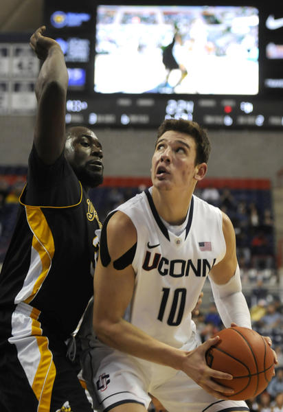 UConn forward Tyler Olander looks to the basket defended by AI guard Spencer Braithwaite during the first half.