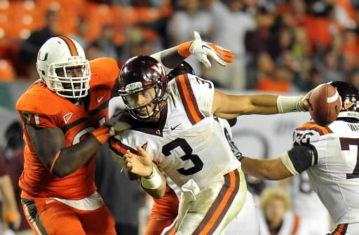 Miami's Olsen Pierre tackles Tech's Logan Thomas