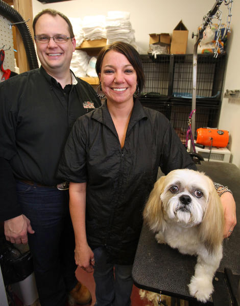 Dean Johnson, owner of Pet Place, left, with groomer, Jo Lynn Lefor, center, and her dog, Sam.
