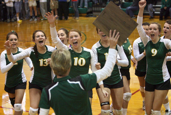 Members of the Aberdeen Roncalli volleyball team celebrate as their coach Janelle Bierle, foreground center, holds up the District 1A Championship trophy after Roncalli defeated Groton for the title at the Roncalli High School gym.
