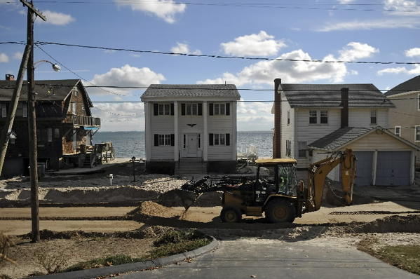 A front loader pushes sand off Shore Road along Oak Grove Beach in East Lyme as residents deal with no power for the fourth day after Hurricane Sandy slammed the state on Monday.