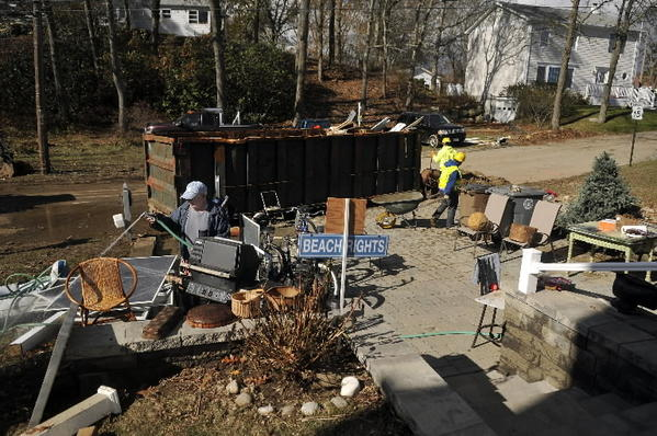 Gene Falcone rinses mud off screens form the basement of his cottage on Shore Road on Oak Grove Beach in East Lyme as residents deal with no power for the fourth day after Hurricane Sandy slammed the state on Monday. Falcone and his wife Gay Reichart are fortunate that they have a couple of generators to keep the refrigerator and a few other appliances working for the time being.