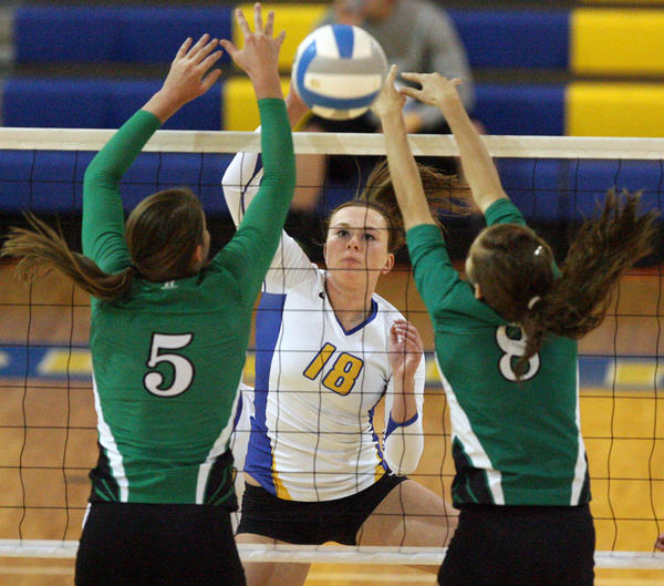 Aberdeen Central's Caitlin Rasmusson, center, tries to hit the ball past Pierre's Kaitlyn Severyn, left and Carly Jo Schroer, right, during Thursday night's District 3AA volleyball match at the Golden Eagles Arena. photo by john davis taken 11/1/2012