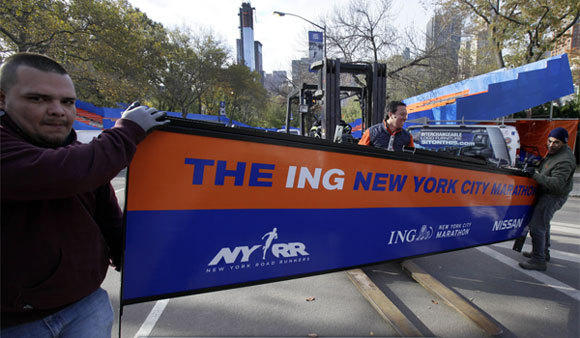 With the crane atop a high-rise that collapsed during Sandy visible in the background, workers assemble the finish line for the New York City Marathon in Central Park on Thursday.