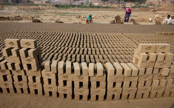 A woman works at a handmade bricks factory in Lahore, Pakistan.