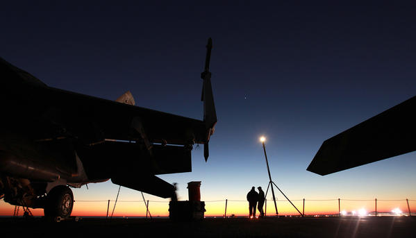 On the deck of the USS Enterprise, F-18s are lashed to the deck as Petty Officer Sean Chester and his brother-in-law watch the sunrise over Naval Station Mayport Friday morning, Nov 2, 2012.