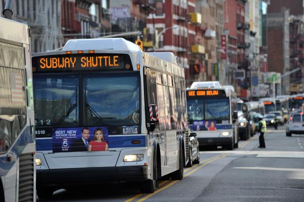 New York City transit buses shuttle passengers down Bowery Street between partially restored subway lines.