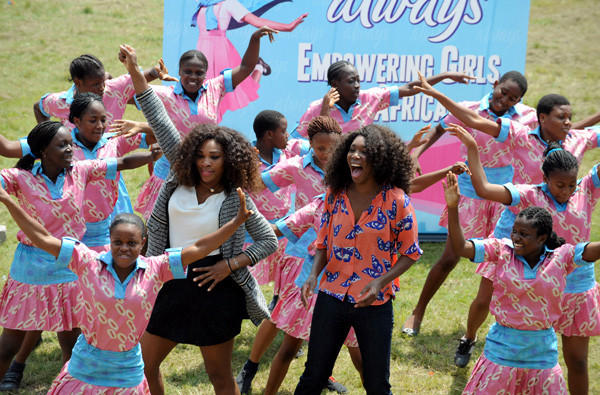 Serena, left, and Venus Williams dance with students of the Federal Government College in Lagos, Nigeria, on Thursday during their tour of Africa.