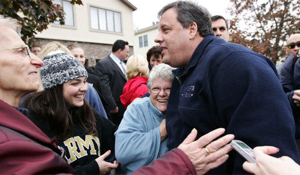 New Jersey Gov. Chris Christie, right, speaks to Martha Gonzalez, center, and other residents of Moonachie, N.J., one of several communities near MetLife Stadium damaged by super storm Sandy.