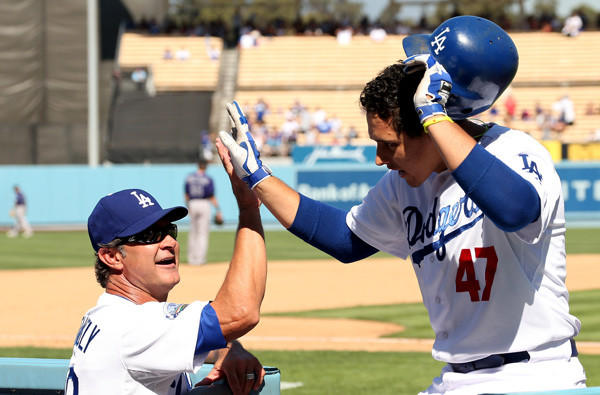Dodgers Manager Don Mattingly high-fives infielder Luis Cruz after he hit a two-run home run against the Rockies.