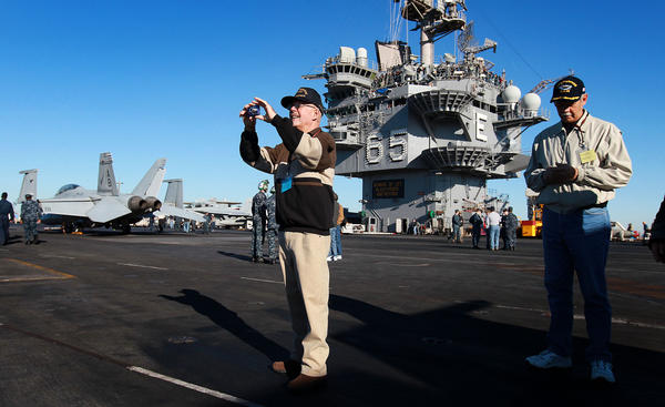 "Former USS Enterprise sailor Ray Godfrey takes photos Friday as he tours the ship he served on for five years. As an original crew member Godfrey is known as ""Plank Owner."""