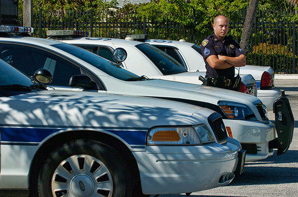 Fort Lauderdale Sergeant Bill Schultz stands next to his take home patrol car parked among other police cars officers take home in the back lot of the Fort Lauderdale Police station Friday afternoon.