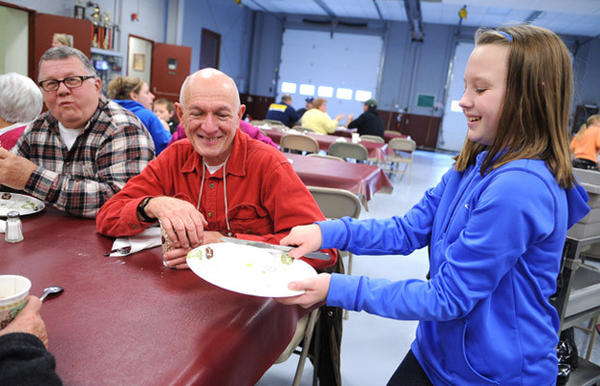 Volunteer Kate Woerner, 11, of Riegelsville, right, clears the table for Joe Chaproniere of Riegelsville, center, and Ken Johnson of Riegelsville at left.