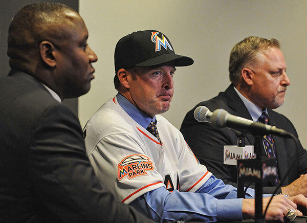 Former Marlins catcher Mike Redmond is introduced during a press conference at Marlins Park in Miami Friday November 2, 2012. General Manager Michael Hill is at left and  president of baseball operations Larry Beinfest is at far right.