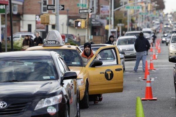 A driver pushes his taxi forward in a line for gasoline in Brooklyn. Gasoline shortages are causing transportation problems everywhere, including JFK airport.