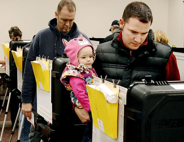 Sophia McCauley watches her dad, Jack McCauley, cast his vote on Friday at the Red Cross Headquarters on the last day of early voting.  The McCauleys live in Boonsboro.
