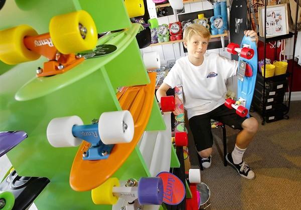 Jordan Pratt, 12, sits at his workshop table where he assembles Penny skateboards at Balboa Boardsports.
