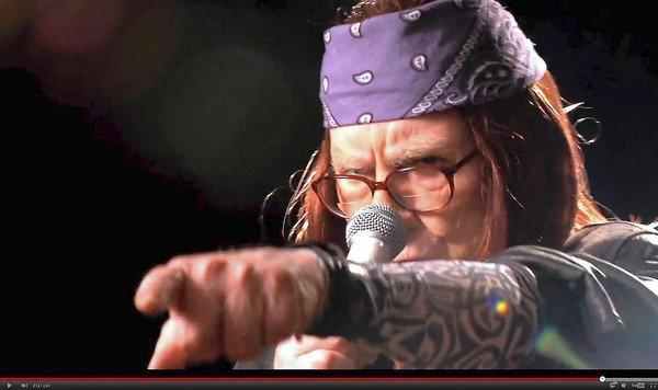 Billionaire investor Warren Buffett, dressed as Axl Rose, sings in a video for a Geico employees meeting. His firm is buying Oriental Trading Co.