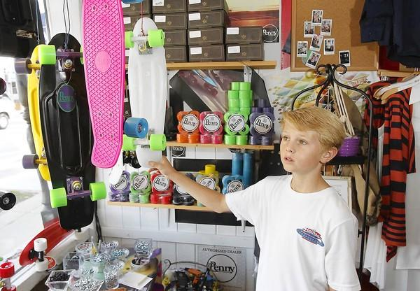 Jordan Pratt, 12, talks about his workshop table where he assembles Penny skateboards at Balboa Boardsports.