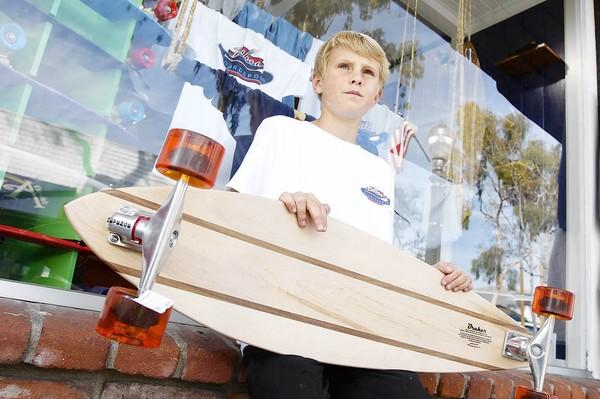 Jordan Pratt, 12, with one of his longboard skateboards at Balboa Boardsports.