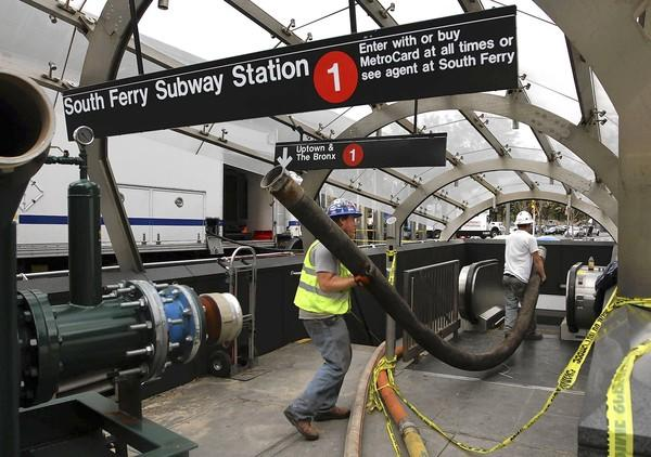 Workers pump water from the subway in Manhattan. Officials said it could still be days before the trains are running again.