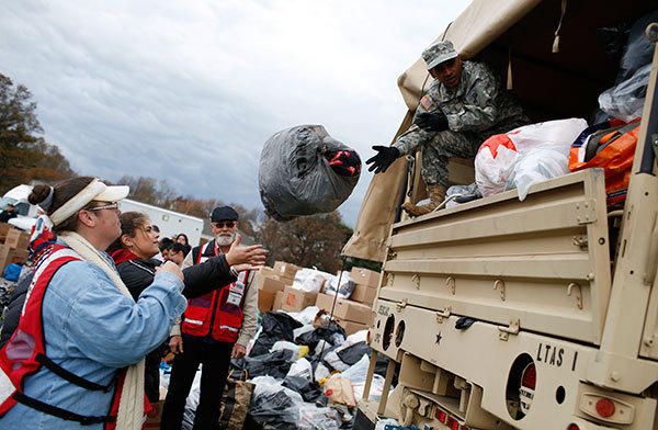 U.S. National Guard and American Red Cross volunteers unload donated supplies for hurricane Sandy victims at a FEMA and American Red Cross aid and disaster relief station in the hard-hit Staten Island section of New York City, November 2, 2012.