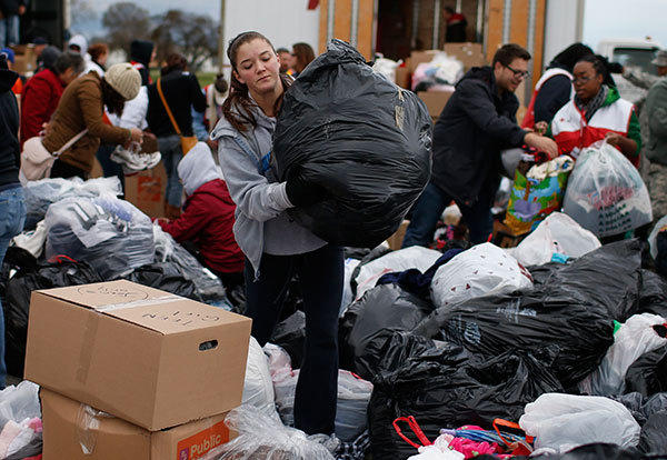 Volunteers sort through piles of donated clothes, food and other items for Hurricane Sandy victims at a FEMA and American Red Cross aid and disaster relief station in the hard-hit Staten Island section of New York City November 2, 2012.