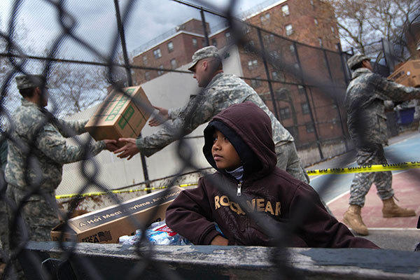 A boy watches as members of the U.S. Army National Guard unload food and supplies in the Rockaways section of the Queens borough of New York November 2, 2012.