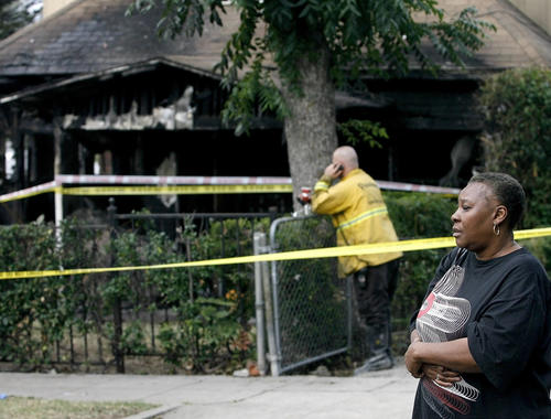 Pamela Clark, estranged wife of one of the two men who died in an early morning fire, stands near the gutted home on the 1300 block of El Sereno Avenue in Pasadena.