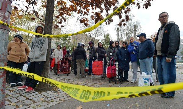 People wait in line to receive food and supplies at a food donation site to help those in areas without power as the city tries to recover from the after effects of Hurricane Sandy in New York.
