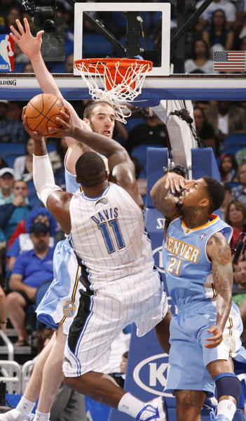 Orlando forward Glen Davis (11) shoots over Denver center Kosta Koufos (41) and Wilson Chandler (21) during the second half of the Magic's 102-89 season opening win over the Nuggets in Orlando, Fla.