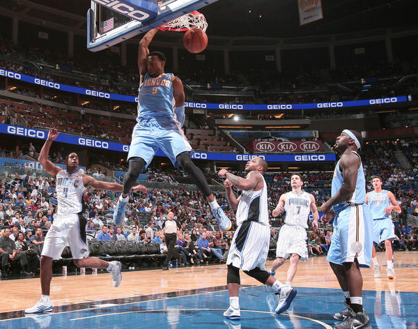 Denver guard Andre Iguodala (9) dunk over Orlando guards Jameer Nelson (14) and Arron Afflalo (4) during the Nuggets' 102-89 loss to the Magic in Orlando, Fla.