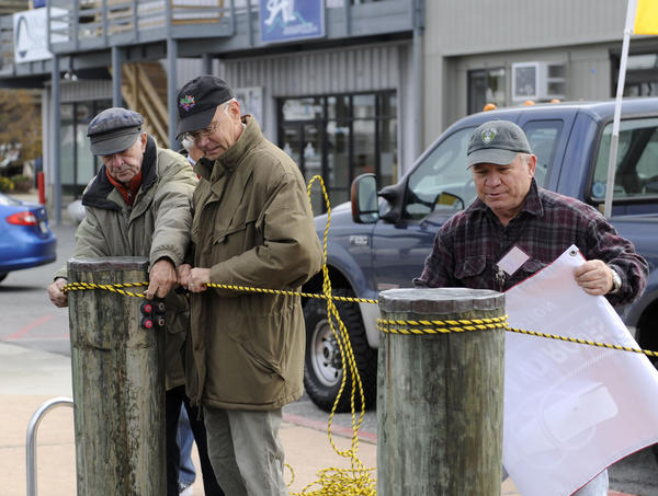 "John Morgan, left, of the Eastport team and Doug Smith, center, of the Annapolis team, and Tom Cagle, right, of the Eastport team, are preparing for the annual ""Slaughter Across the Water,"" a tug of war contest between Annapolis and Eastport.  Here, they stretch a rope across pilings on the Eastport side."