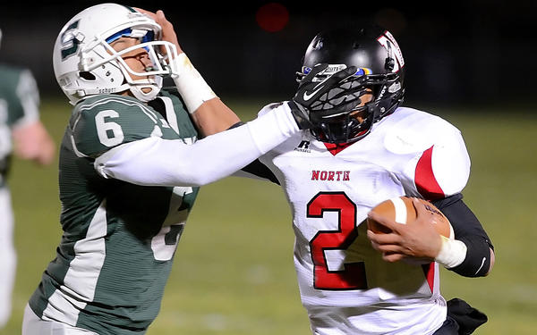 North Hagerstown's Isaiah Keyes (2) tries to break through the high tackle attempt of South Hagerstown's Jakerian Jones (6) during Friday night's Hagerstown Gridiron Championship Classic at School Stadium. The Hubs won to finish unbeaten in the MVAL Antietam and earn a playoff berth.
