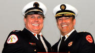 Capt. Herbert Johnson (left), with Fire Cmsr. Jose Santiago, at the ceremony where Johnson was made a captain this summer. Fire Department photo
