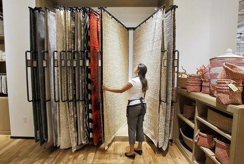 Studio designer Jessica Muro looks over a few rugs at the new West Elm home furnishings store in the Macy's Home Wing at South Coast Plaza.