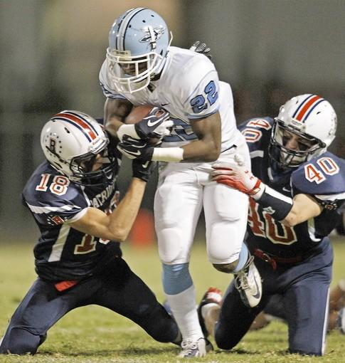 Corona del Mar High's Kai Wilson (22) battles for yardage against Beckman's Marcus Volpe (18) and Ryan Haughton (40).