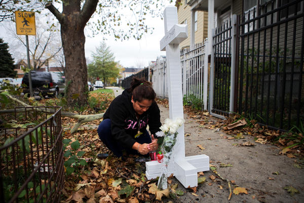 Catalina Andrade lights a candle at a memorial near the scene of a house fire on Saturday where Capt. Herbert Johnson was killed. Johnson died fighting a fire on Friday night in the Gage park neighborhood.
