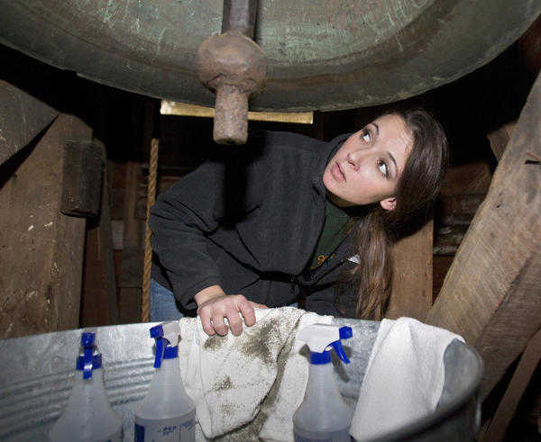Caitlyn Darnell examines historic graffiti while helping to clean the bell at Bruton Parish Episcopal Church in Colonial Williamsburg on Saturday.