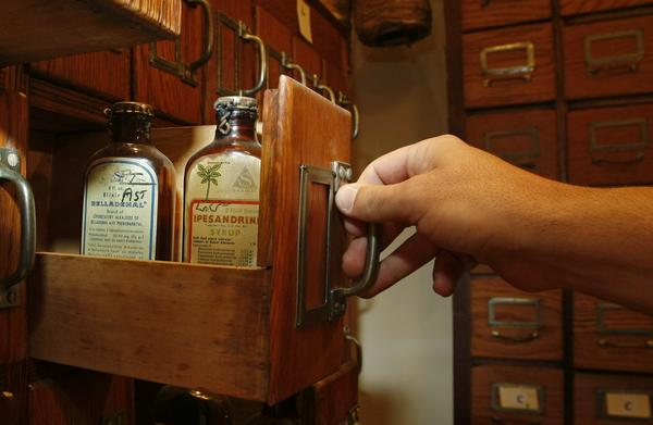 "A file cabinet drawer in the pharmacy holds bottles whose labels list ingredients such as morphine, narcotine, and phenobarbital-- and a warning, ""MAY BE HABIT FORMING""."