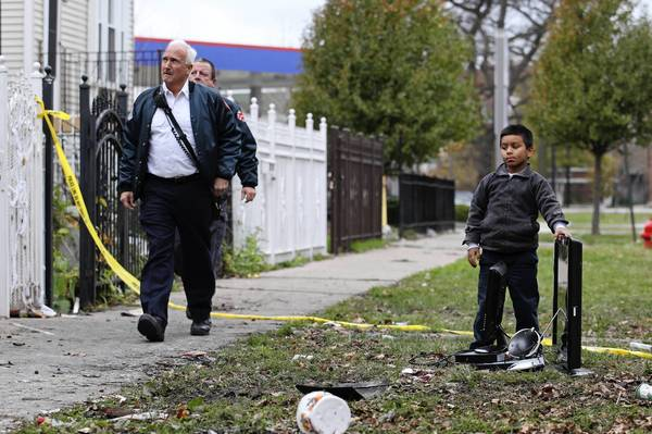 Christian Castaneda, 5, stands with his family's possessions, while left, members of the Chicago Fire Department come to see the scene of the fire that killed their friend, Capt. Herbert Johnson, at 2315 W. 50th Pl., in Chicago.