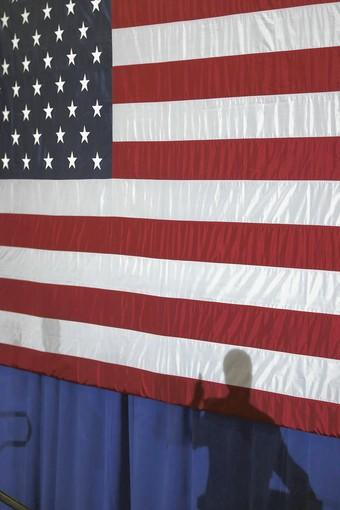 Vice President Joe Biden casts a shadow on the flag as he speaks at a rally Friday in Beloit, Wis.