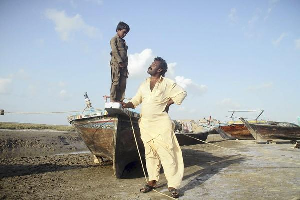 Nooro Mala, a fisherman from the village of Shah Bandar, pictured with his son, doubts that Pakistani President Asif Ali Zardari's dream metropolis on the tidal flats of the Indus River Delta can ever be built.