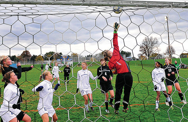 Williamsport goalie Julia Price, in red shirt, leaps unsuccessfully at a corner kick during the first half of Saturday's Maryland Class 2A West girls soccer semifinal against Oakdale. The Wildcats successfully defended the play.