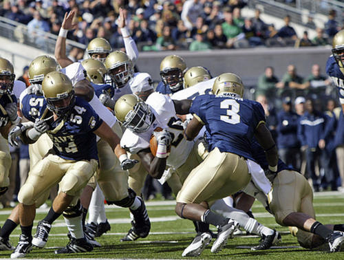Notre Dame running back Cierre Wood (20) is stopped by Navy's Taylor Simmons (54) and De-Von Richardson (3) inside the one yard-line on third down in the second quarter.